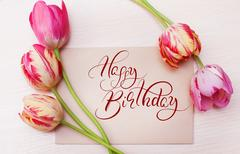 Bouquet of red tulips on white background with text Happy Birthday. Calligraphy Stock Photos