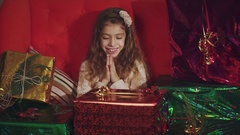 Happy girl around christmas presents rejoices and claps. Concept of gift. Stock Footage