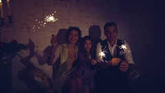 Happy family and bengal fire or sparklers lights in dark room at christmas eve Stock Footage