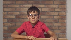 Child sitting at the desk holding flipchart with lettering time on the Stock Footage