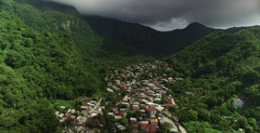 Aerial pulling back out of the entire valley to reveal coastal town under clouds Stock Footage