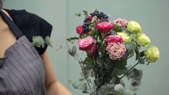 Florist recruit bunch of flower to create composition inside Stock Footage