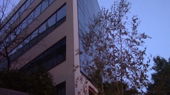 View of the corner of a glass building at dusk Stock Footage