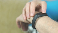 Woman looks at the wristband fitness tracker Stock Footage