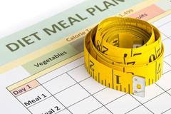 Dieting weight loss concept - measurement tape on meal planning form Stock Photos