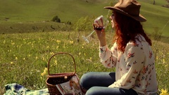 Woman in a hat drinking wine sitting on a green meadow high in the mountains Stock Footage