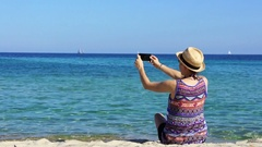 Young woman uses a smartphone to video a beautiful view at the beach HD Stock Footage