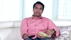 Young man watching tv at home Stock Footage