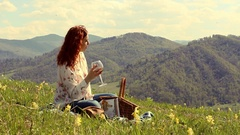 Woman drinking wine sitting on a green meadow high in the mountains Stock Footage