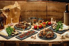Fried meat, marinated vegetables,  potatoes, greens, spetsiin slate black plates Stock Photos