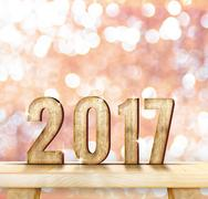 2017 year wood number on wood table with pink sparkling Stock Photos