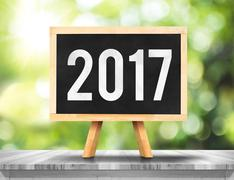 2017 new year on blackboard on plank white wood with blur tree Stock Photos
