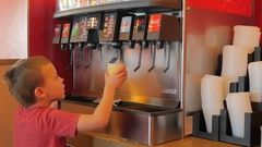 Young boy getting soda pop from a fountain machine Stock Footage