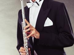 Elegantly dressed musician holding flute Stock Photos