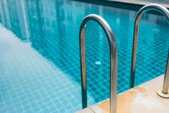 Blue swimming pool with condominium reflect in the water. Stock Photos