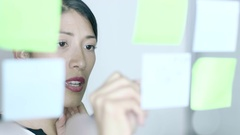 Native American Woman writing notes on window in creative office Stock Footage