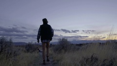 Young Man Walks (Away From Camera) His Dog On Trail At Sunset Arkistovideo