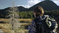Adventurous Young Man Hikes Along Trail Through Wilderness (Shot From Behind) Stock Footage