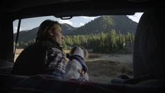 Adventurous Young Man Sits In Back Of SUV With Dog, Pets Her, Looks Out At View Stock Footage