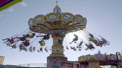 Swing chair ride with people in wide shot zooming in, Santa Cruz amusement park Stock Footage