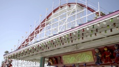 People, rides and roller coaster in crowded amusement park at Santa Cruz Stock Footage