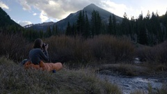 Young Man Sits Inside His Sleeping Bag, And Photographs Mountain Landscape Stock Footage