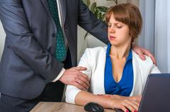 Man touching woman's shoulder - sexual harassment in business office Stock Photos
