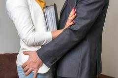 Man touching woman's butt - sexual harassment in business office Stock Photos
