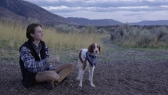 Man Sits On Trail And Gestures For His Dog To Sit, Gives Her A Treat Stock Footage