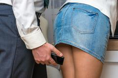 Man taking photo with mobile phone of woman's butt Stock Photos