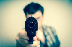 Crazy young man aiming gun at you Stock Photos