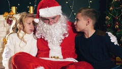 Santa and children around the decorated Christmas tree. Wishes list Stock Footage