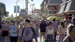 Young man on headphones, boy with earbuds walking in crowded amusement park Stock Footage