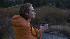 Profile Of Adventurous Young Man, Stands In Sleeping Bag, Drinking From Mug Stock Footage