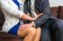 Man touching woman's knee - sexual harassment in business office Stock Photos
