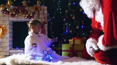 Santa and girl playing near fireplace, decorated Christmas tree Stock Footage
