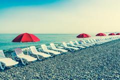 Beach chairs or beds and sun red umbrellas on the beach Stock Photos