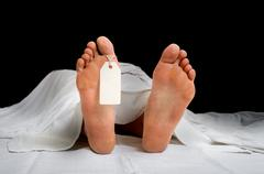 The dead woman's body with blank tag on feet under white cloth in a morgue Stock Photos