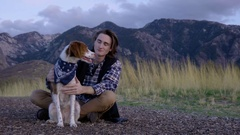 Adventurous Young Man Sits With His Dog And Watches The Sunset, He Pets Her Stock Footage