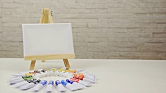 Zoom-in to mini easel with canvas and color tubes under 4K Stock Footage