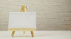 Empty canvas on mini easel alone on table slide from right to left 4K Stock Footage