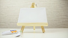 Easel with canvas and tubes on table low angle dolly slide 4K Stock Footage