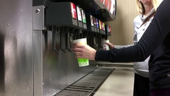Young women selecting cool fountain drink from self service soda machine Stock Footage