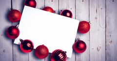 Composite image of red christmas baubles surrounding white page Stock Photos