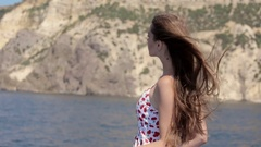 Pretty girl with long straight hair is on the board of the boat in windy weather Stock Footage