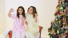 Two girls having fun in their pajamas near the Christmas tree Stock Footage