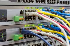 Telecommunications rack with switches and colored patch cords Stock Photos