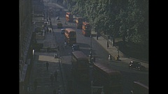 Vintage 16mm film, 1953 London street scene, high angle buses, people on street Stock Footage