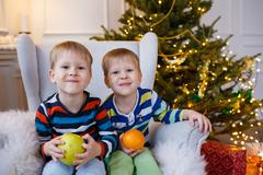 Two little smiling kids, boys keep fruits - apple and orange on Christmas tree Stock Photos