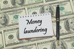 Notebook page with text MONEY LAUNDERING on dollar background Stock Photos